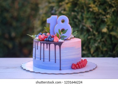 beautiful homemade birthday cake with the number eighteen, decorated with fresh blueberries, currants and strawberries. natural green background