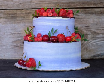 beautiful homemade two-tiered cake with purple cheese cream, decorated with cherries, raspberries, strawberries, on a wooden background