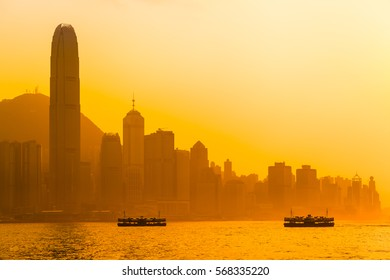Beautiful Hong Kong cityscape view at orange sunset light with two ships, tall buildings and Peak mountain (copy space)/Hong Kong Evening Sky