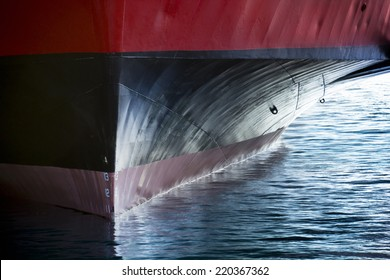 A beautiful horizontal graphic view of the bow of a large ship in port. It would make a great background image for anything involving international shipping; transportation; industrial cargo or trade.