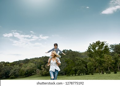 Beautiful horizontal image of cute little girl on a piggy back ride with her happy mother. Loving woman and her daughter playing in the park. Mom and kid has fun. Mother's day