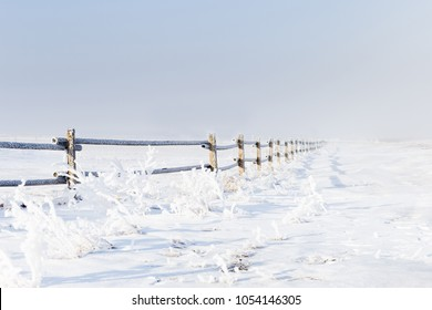beautiful horizontal image of a snow and frost covered wooden fence running into the  foggy and misty distance on an early morning winter day.
