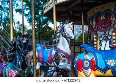 Beautiful horse Christmas carousel in a holiday park. Horses on a traditional fairground vintage carousel. Merry-go-round with horses.