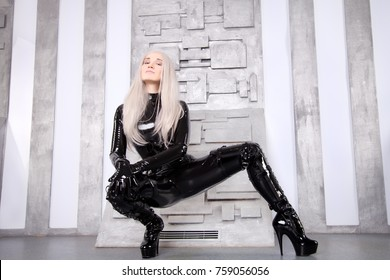 Beautiful Hot Sexual Fetish Woman Wearing Shiny Black Latex Rubber Catsuit and Corset on Gray Futuristic  Background