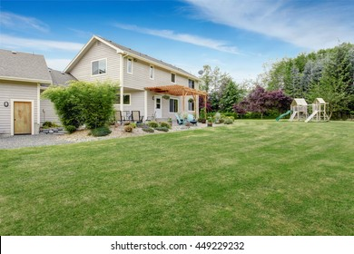 Beautiful house backyard with well kept lawn, patio area and playground at the background
