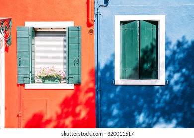 Beautiful house facade on Burano island, north Italy. Old damaged half blue,half red house wall with a door and some windows.