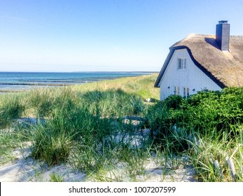 beautiful house with Roof ree or thatch on the beach between the dunes while morning