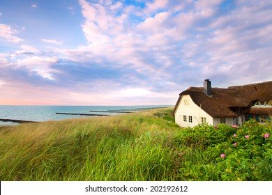 beautiful house with Roof ree or thatch on the beach between the dunes while sunset