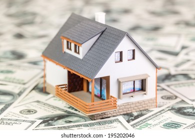 Beautiful house standing on 100 dollar bills. House expenses or investing concept.