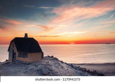 Beautiful House in typical yellow color on the beach with sea view during colorful sunset. Skagen coastline in North Jutland in Denmark, Skagerrak, North Sea