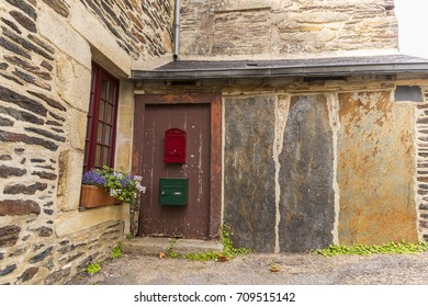 Beautiful house with wooden door and window, lots of flowers and granite walls