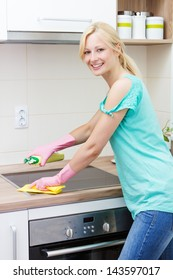 Beautiful housewife cleaning in the kitchen.