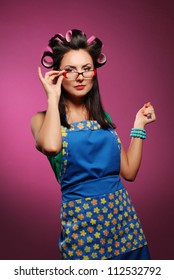 Beautiful housewife in glasses on the pink background