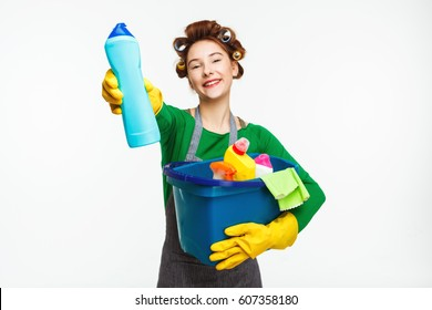 Beautiful housewife holds cleaning tools and shows bottle