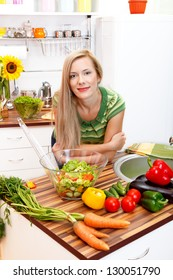 Beautiful housewife in the kitchen with healthy fresh vegetables and salad