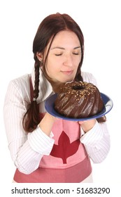 beautiful housewife smelling bundt cake on white background