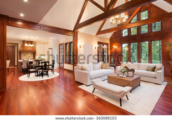 Beautiful and  huge living room with hardwood floors, tall vaulted ceiling, fireplace and couch in new luxury home. Has view of kitchen