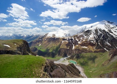 Beautiful huge mountains peaks in snow, blue sky, white clouds, blue lake at the foot of the mountain, green hills, green valley background, top view, Georgia