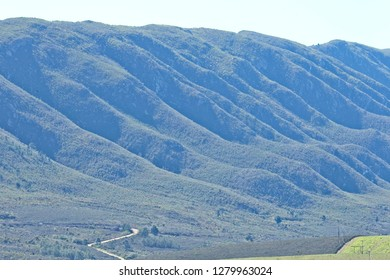 Beautiful huge rolling hills in morning sun with a road entering from the bottom left