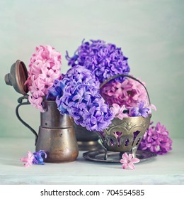 Beautiful hyacinth flowers in a copper pitcher on a textural background.  Beautiful bouquet for a birthday.