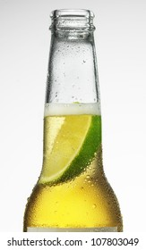 Beautiful ice cold beer in a bottle with a wedge of fresh lime