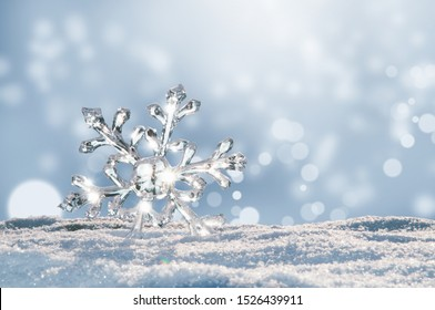 Beautiful ice crystal lies in the snow and glistens in the sun, bokeh in the blue background