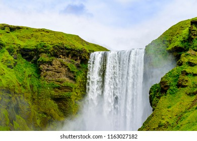 Beautiful Iceland Skogafoss waterfall with water spray. Moss covered green hills and rock formations. Cows, sheep and people. Blue skies.