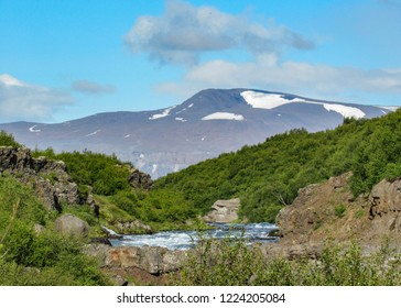 Beautiful Icelandic summer landscape close to Hraunfossar with mountains, azur Hvita River, green forest vegetation and blue sky with clouds in Borgarfjordur region, West Iceland, Europe