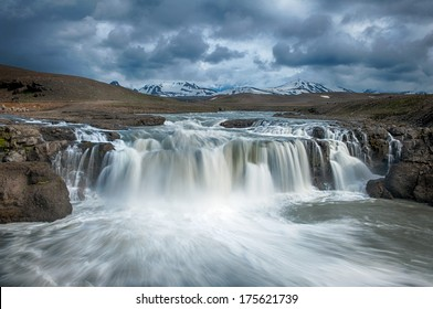 Beautiful Icelandic waterfall with dramatic sky. It is located in the centre of the island, near Kjolur road.