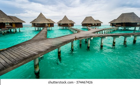 Beautiful and idyllic tourist destination place with floating wooden thatched roof wooden luxury resort houses of Maldive Islands