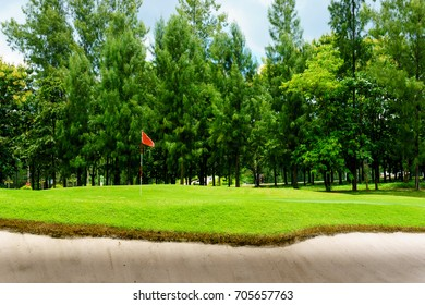 beautiful idyllic view of green with sand trap and red flag and view of forest, blue sky with clouds