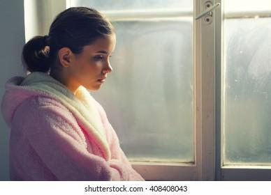 Beautiful ill sad girl in night gown looking through hospital window.
