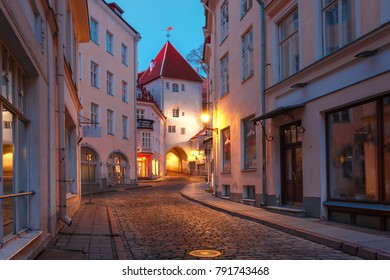 Beautiful illuminated medieval street in Old Town of Tallinn during evening blue hour, Estonia