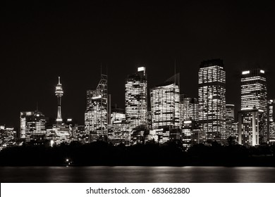 Beautiful illuminated Sydney CBD Skyline at night, in black and white, with reflections in water, as seen from Farm Cove Bay in Sydney Harbour, Australia.
