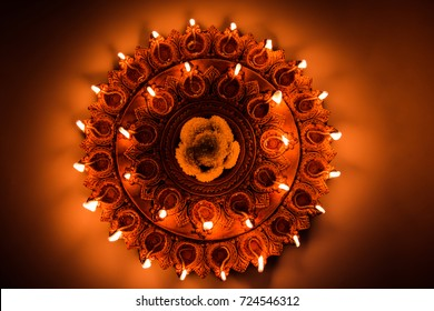 Beautiful illuminated terra-cotta Diwali diya Plate in the night, moody lighting, selective focus
