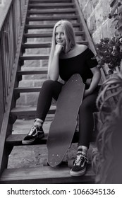 Beautiful image of a blonde skater girl sitting on the stairs wih her longboard in her hand.