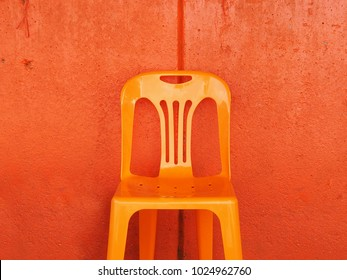 The beautiful image of the clean orange  urban vintage plastic chair in the center of of red rough  texture concrete wall background in harmony mood, vintage retro style