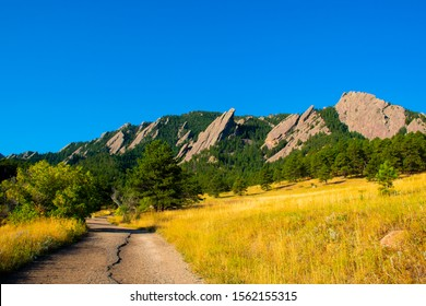 beautiful image of the Flatirons dark granite mountains from below with green and yellow lawns, in Chautauqua Park in Boulder Colorado