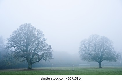 Beautiful image of foggy misty forest in Autumn Fall ith football soccer pitches