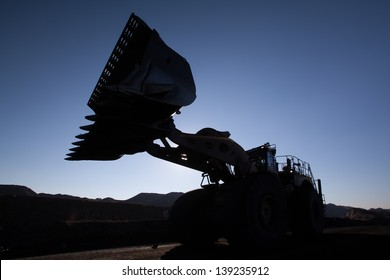 beautiful image of front loader working on a mine at sunrise