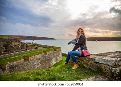 Beautiful image of Kinsale fort in Ireland, woman is sitting on the fort wall and admire stunning Ireland nature