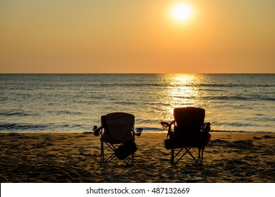A beautiful image of a sunrise at the beach with two folding chairs. Captured in Virginia Beach.