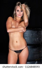 A beautiful implied blonde model posing against racing tires in a studio environment