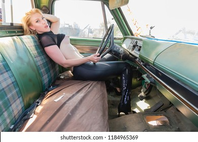 A beautiful implied blonde model posing in a auto salvage yard.