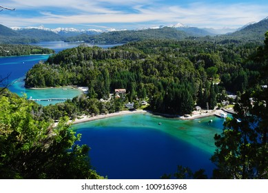 Beautiful incredible view of a blue, green and turquoise bay of a lake, surrounded by a forest and with the Andes in the horizon, Villa la Angostura, Argentina