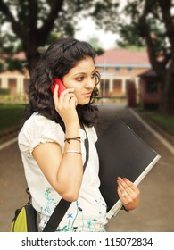 Beautiful Indian / Asian colege student talking on her Cellphone.