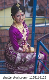 Beautiful Indian Bengali bride is sitting on rooftop staircase in bridal make up and jewelry Indian lifestyle and culture
