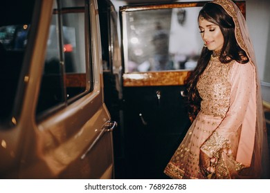 Beautiful Indian bride in pink dress  and veil embroidered with gold stands before a white retro car