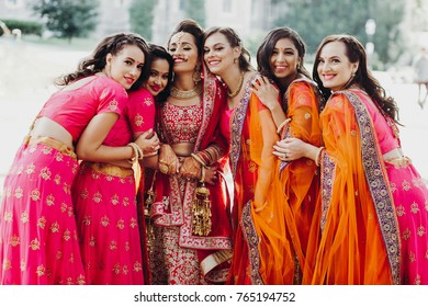 Beautiful Indian bride in red lehenga embroidered with gold poses with her pretty Hindu bridesmaids outside