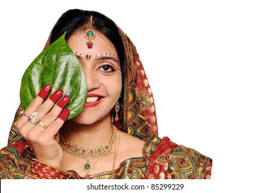 Beautiful Indian bride in red sari holding a green leaf. She looks stunning!!!